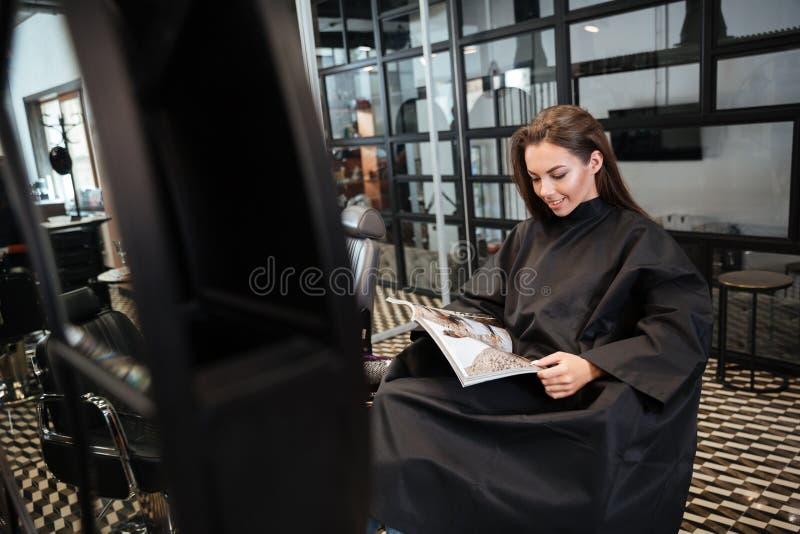 Kvinnasammanträde i skönhetsalong och läs- modetidskrift royaltyfria bilder