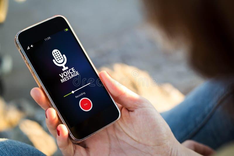 kvinnasammanträde i smartphonen för messageher för gatainspelningstämma royaltyfri bild