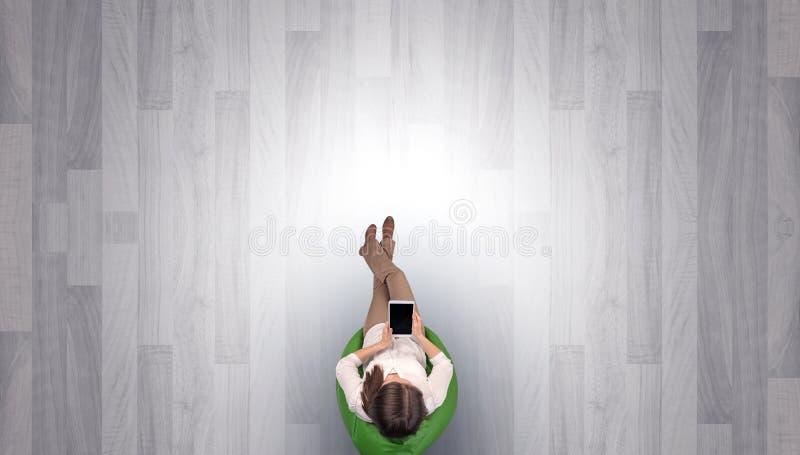 Kvinnasammanträde i stol i ett tomt kontor fotografering för bildbyråer