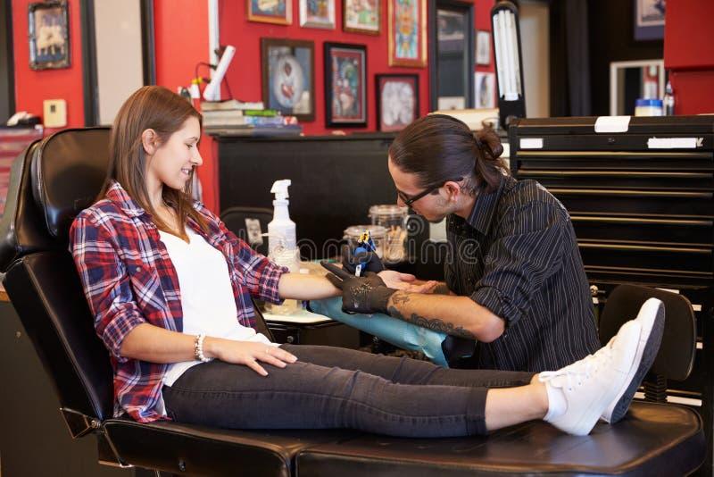 Kvinnasammanträde i stol som har tatueringen på armen i mottagningsrum royaltyfri foto