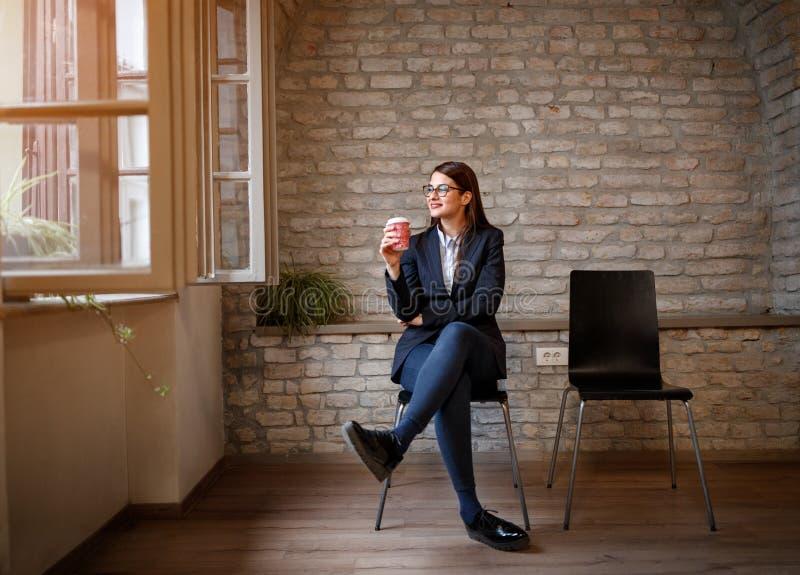 Kvinnasammanträde i studio med koppen kaffe fotografering för bildbyråer