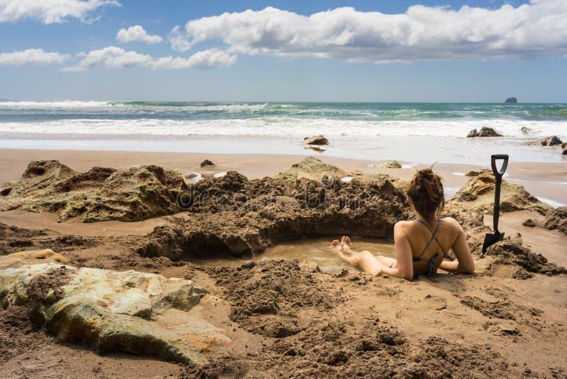 Kvinnasammanträde i termisk pöl för varmvatten i varmvattenstrand royaltyfri fotografi