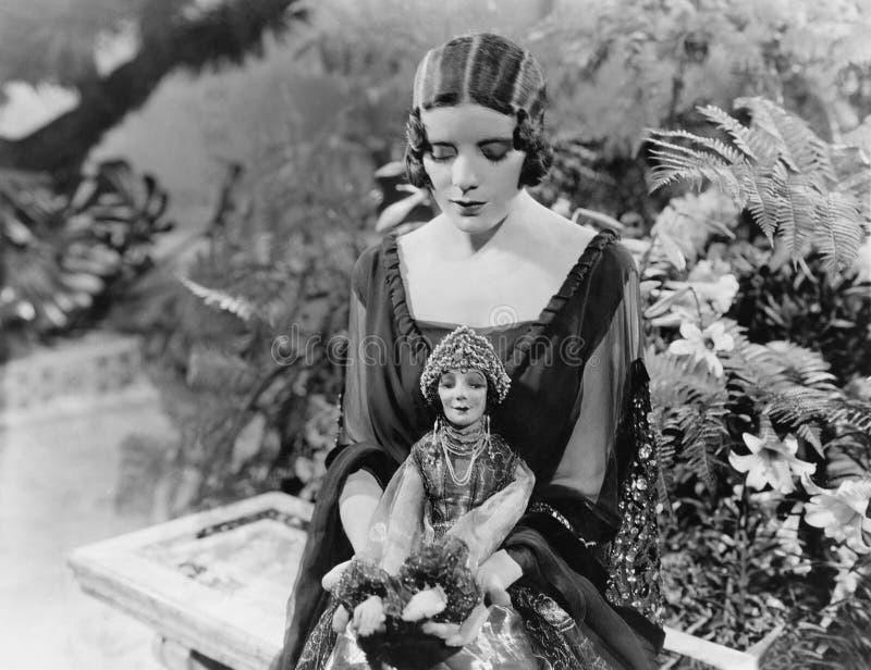 Kvinnasammanträde i trädgård med dockan (alla visade personer inte är längre uppehälle, och inget gods finns Leverantörgarantier  arkivfoto