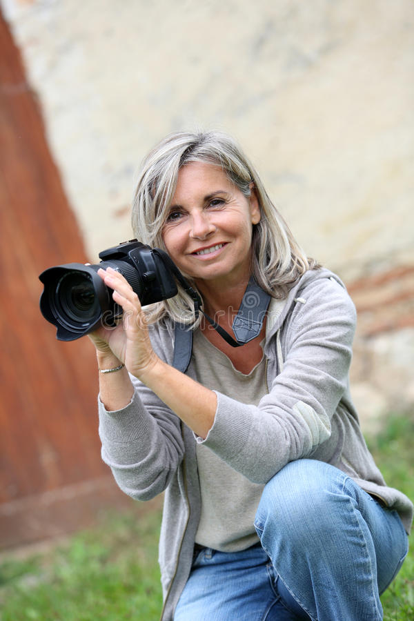 Kvinnasammanträde i trädgården som tar bilder fotografering för bildbyråer