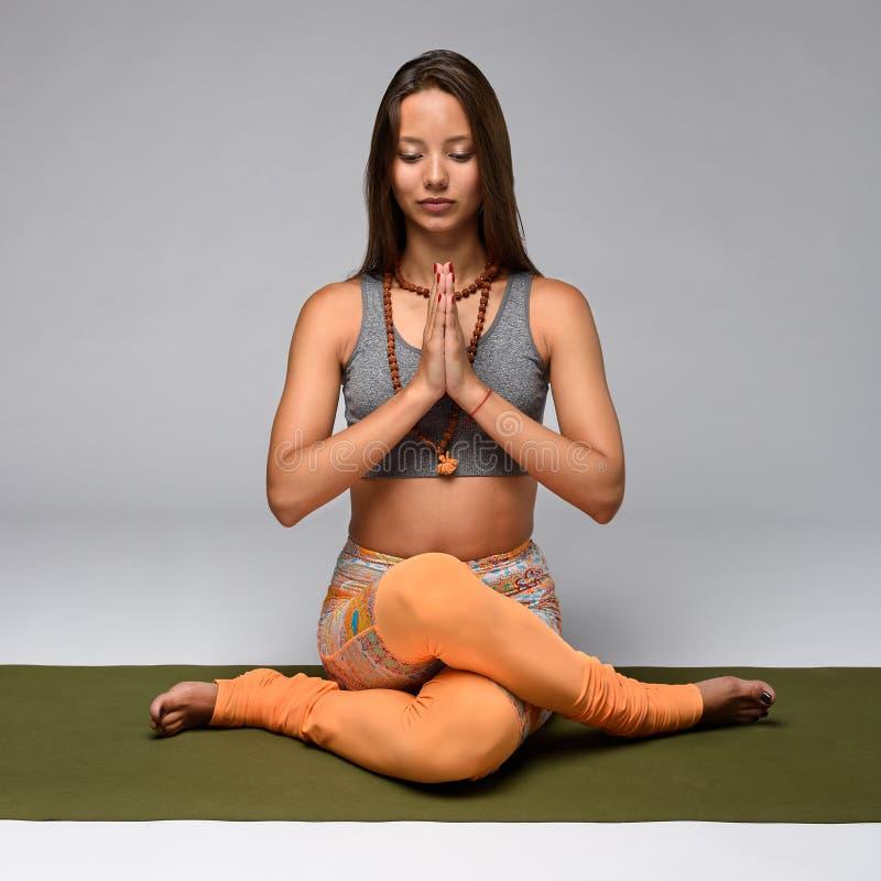 Kvinnasammanträde i yoga poserar royaltyfri fotografi