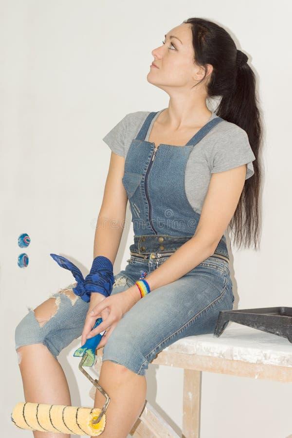Kvinnasammanträde med en målarfärgrulle royaltyfri fotografi