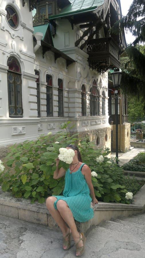 Kvinnasammanträde med gruppen av blommor som döljer framsidan royaltyfri bild