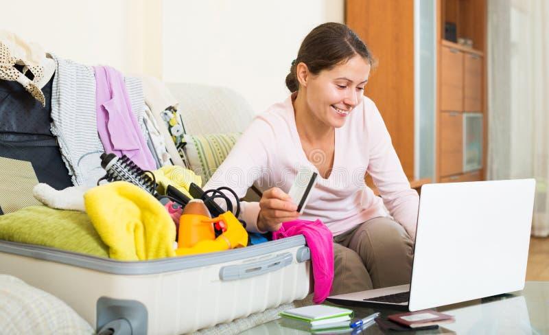 Kvinnasammanträde med kreditkorten nära bärbara datorn och bagage royaltyfri bild