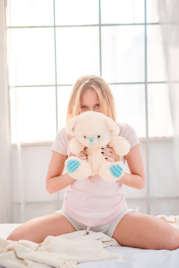 Kvinnasammanträde med nallebjörnen på sängen royaltyfria foton
