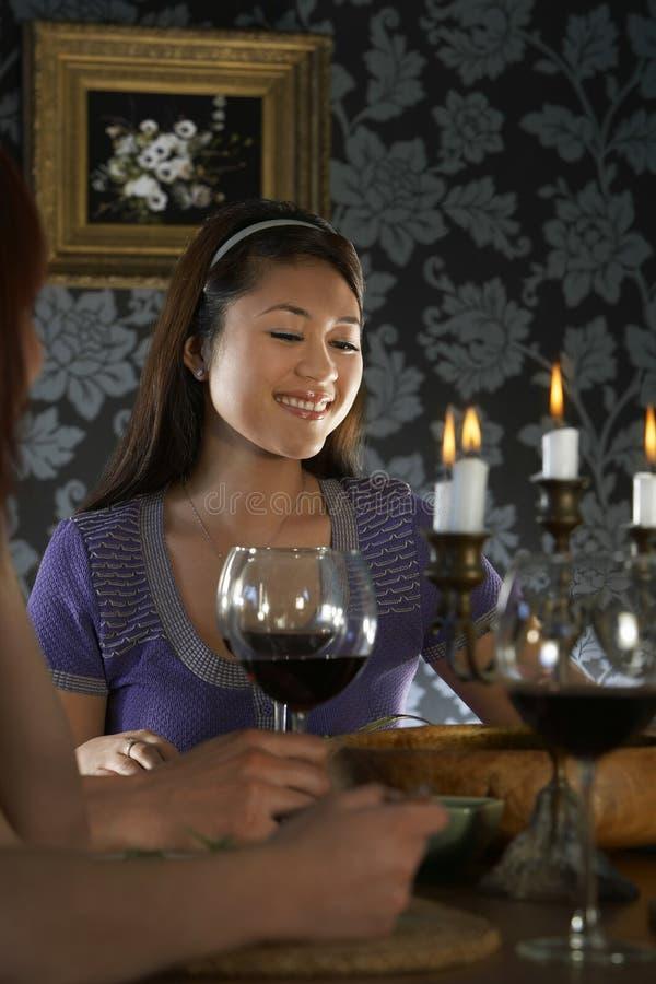 Kvinnasammanträde med vänner på att äta middag tabellen royaltyfri foto