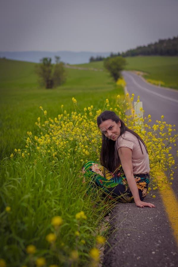 Kvinnasammanträde nära vägen arkivfoton