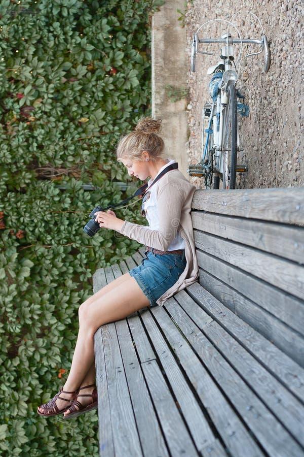 Kvinnasammanträde på bänk i abstrakt miljö royaltyfri foto