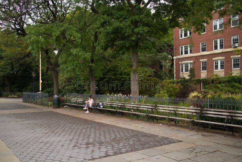 Kvinnasammanträde på bänken, Brooklyn Heights promenad royaltyfria foton