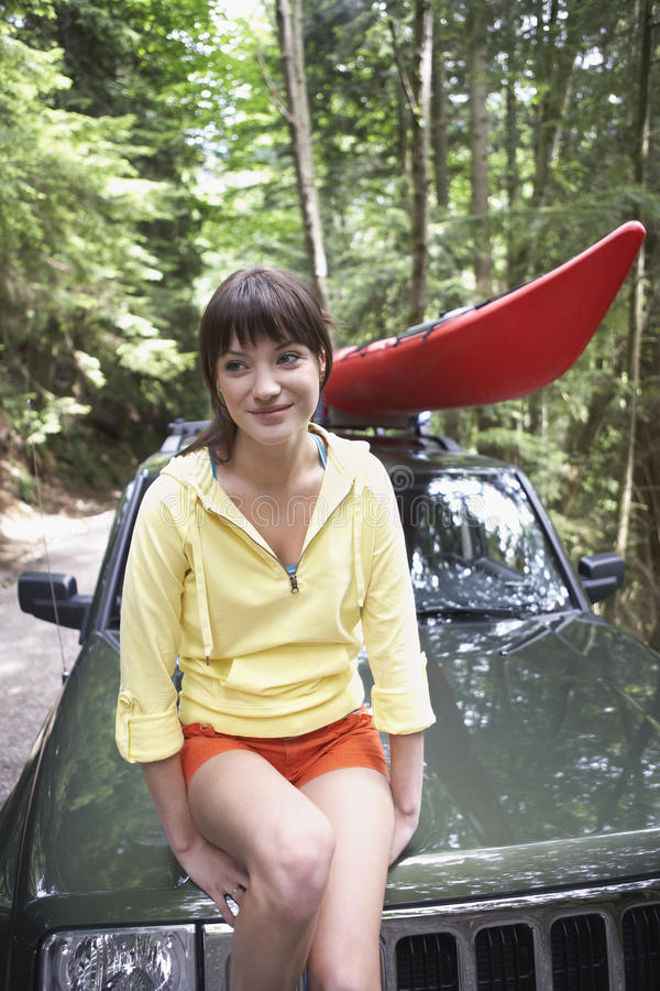 Kvinnasammanträde på bilhättan i skog arkivfoto