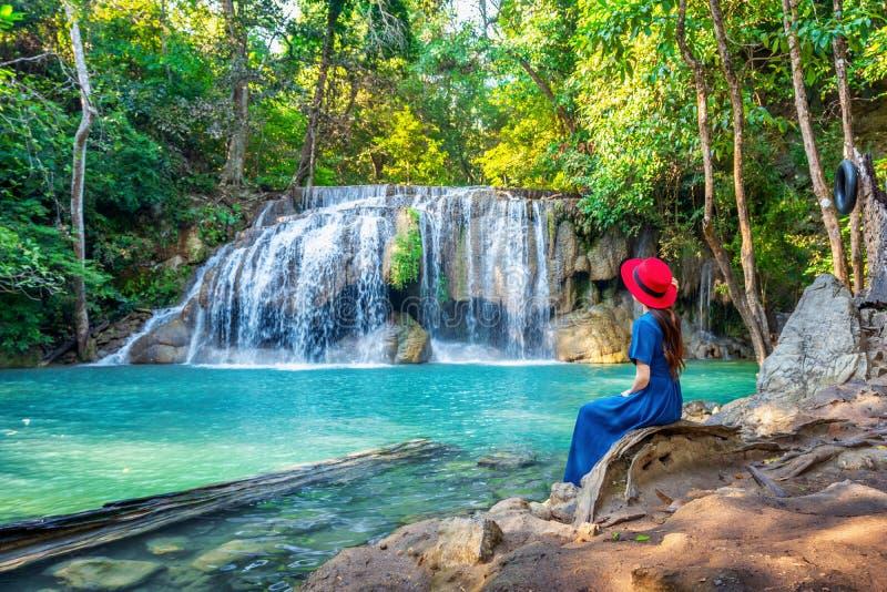 Kvinnasammanträde på den Erawan vattenfallet i Thailand Härlig vattenfall med smaragdpölen i natur royaltyfria bilder