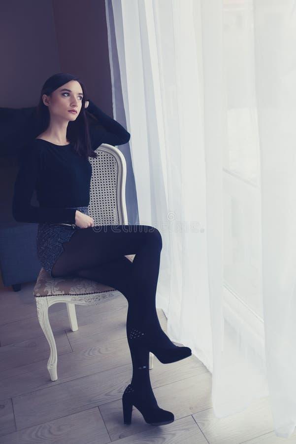 Kvinnasammanträde på den gammalmodiga stolen nära fönster royaltyfri foto
