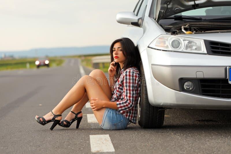 Kvinnasammanträde på den jordnear brutna bilen royaltyfri bild