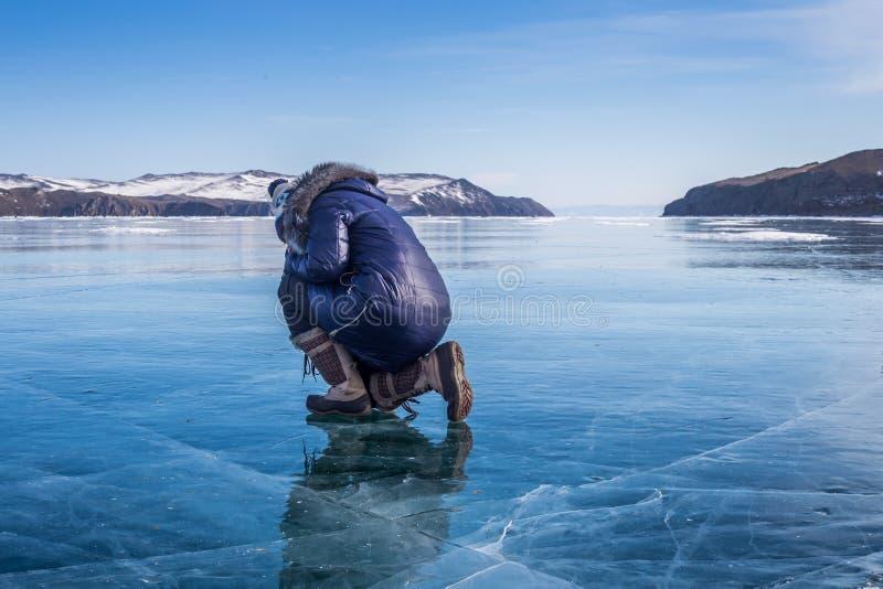 Kvinnasammanträde på det djupfrysta Laket Baikal royaltyfria bilder