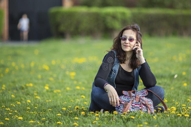 Kvinnasammanträde på det gröna gräset talar på hans mobiltelefon fotografering för bildbyråer