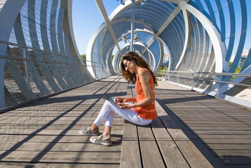 Kvinnasammanträde på det moderna stället i staden som surfar internet i minnestavla arkivfoto