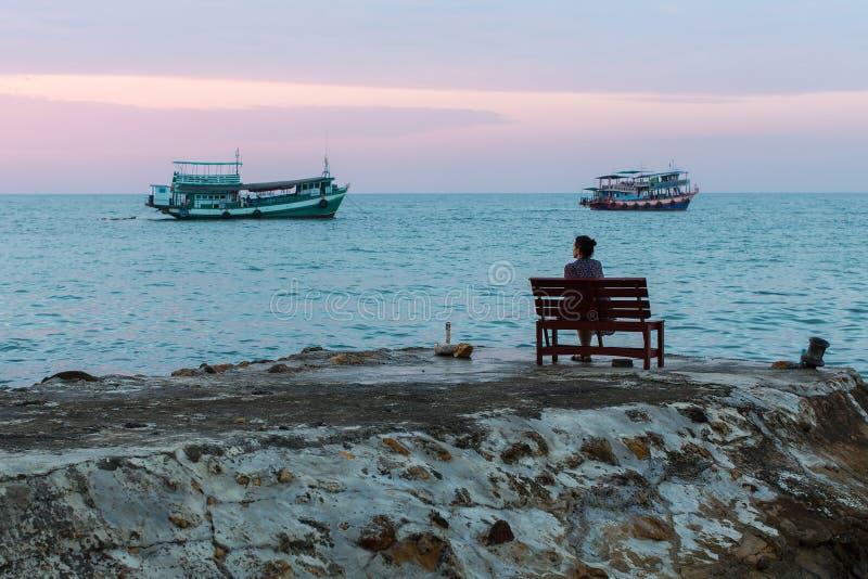 Kvinnasammanträde på en bänk nära havet i aftonen royaltyfria foton