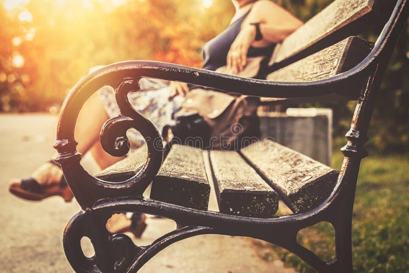 Kvinnasammanträde på en bänk, vila, en påse och en kamera bredvid henne, solinställning bak henne royaltyfri bild