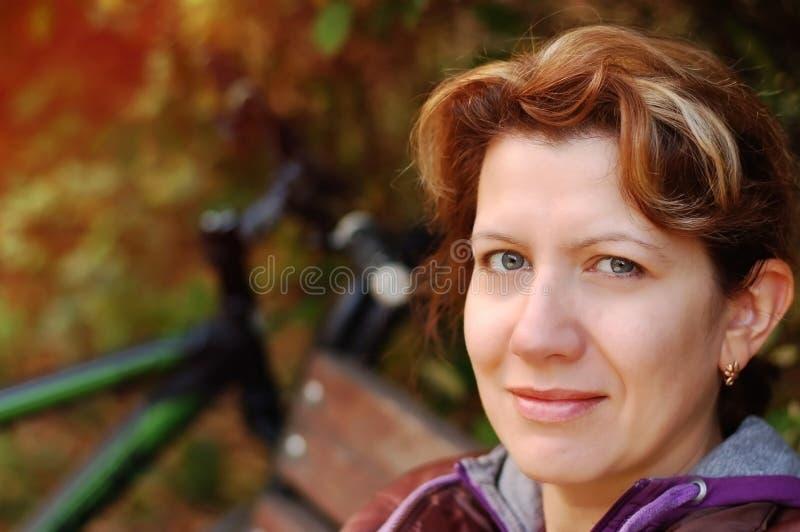Kvinnasammanträde på en parkerabänk, når att ha cyklat royaltyfri foto