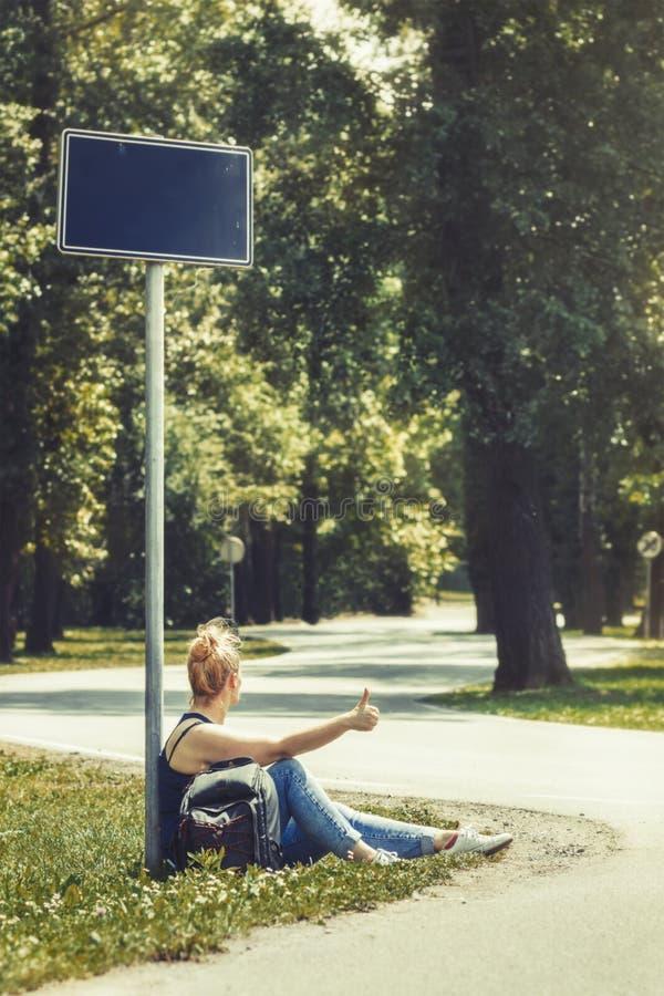 Kvinnasammanträde på en sida av vägen under gatatecknet som omges av träd som liftar royaltyfria bilder