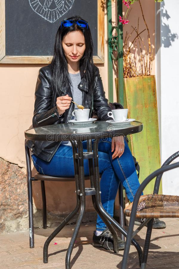 Kvinnasammanträde på en tabell på gatan och drickakaffet royaltyfri bild