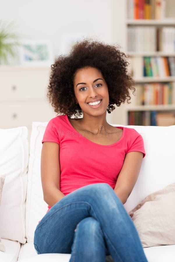 Kvinnasammanträde på en vit soffa, i vardagsrummet fotografering för bildbyråer