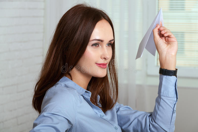 Kvinnasammanträde på ett skrivbord, i ett kontor och att kasta det pappers- planet arkivfoto