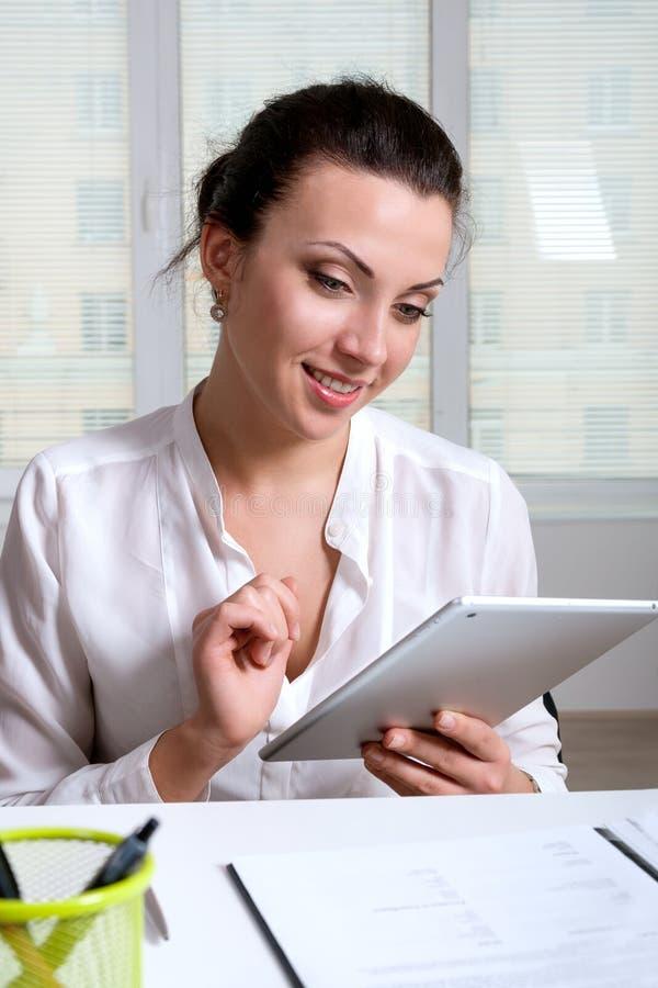 Kvinnasammanträde på ett skrivbord i ett kontor studerar informationen royaltyfri fotografi