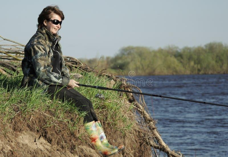 Kvinnasammanträde på flodbanken med metspöet i hand arkivfoto