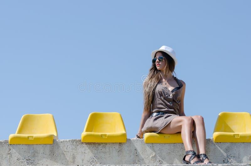 Kvinnasammanträde på gul stadionstol royaltyfri fotografi