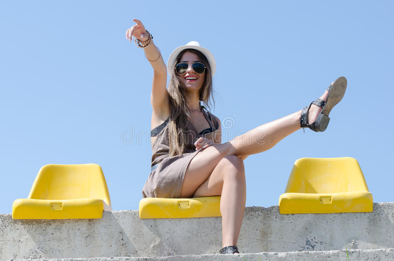 Kvinnasammanträde på gul stadionstol arkivfoto