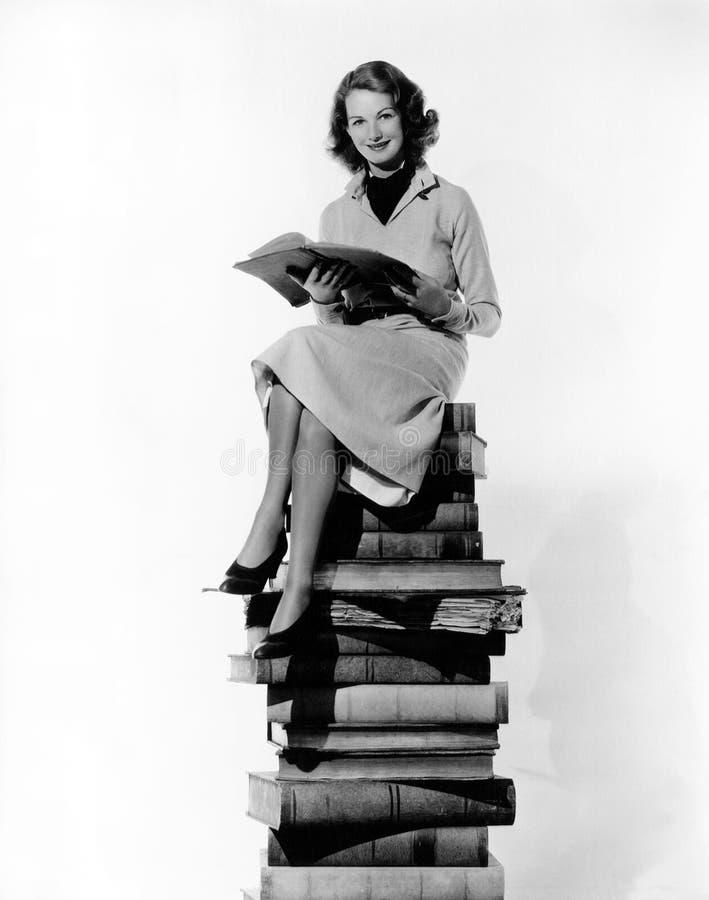 Kvinnasammanträde på högen av böcker (alla visade personer inte är längre uppehälle, och inget gods finns Leverantörgarantier som royaltyfria foton