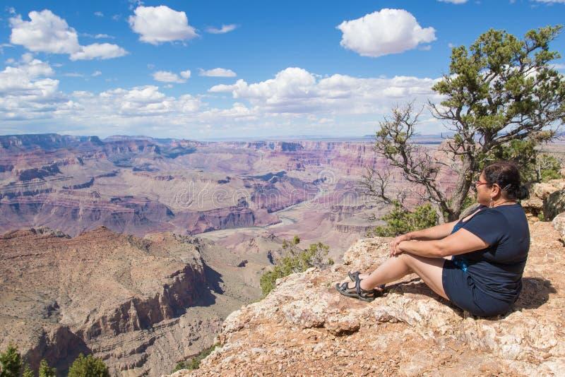 Kvinnasammanträde på kanten av Grand Canyon royaltyfri bild