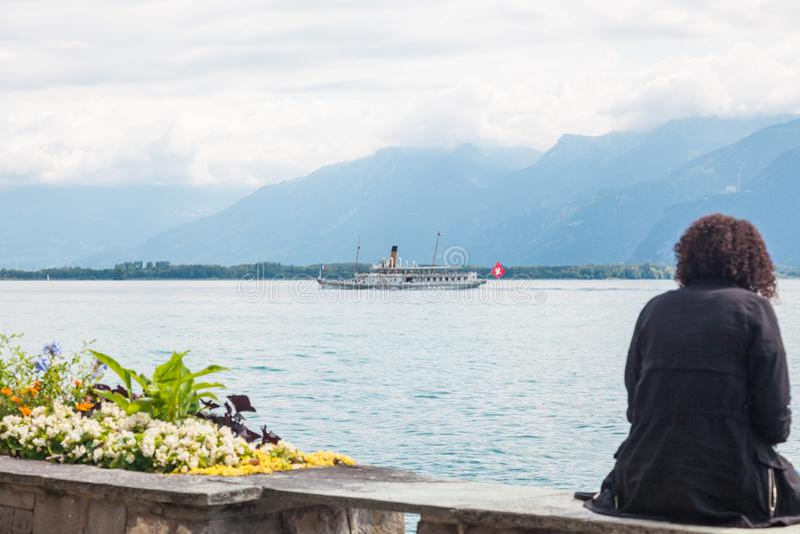 Kvinnasammanträde på Montreux promenad och tycka omsikter av sjöGenèvegummilacka Leman och den traditionella skovelångbåten som k royaltyfri foto