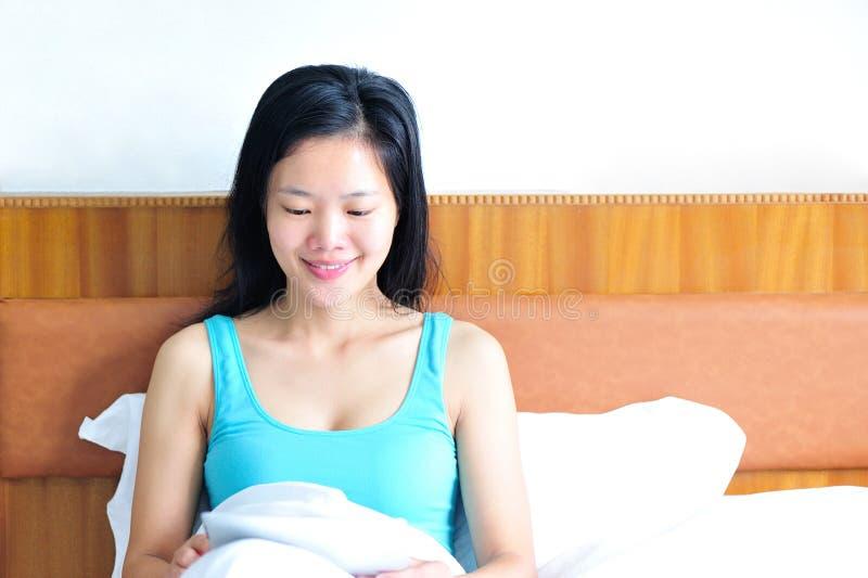 Kvinnasammanträde på sängen genom att använda hennes minnestavla royaltyfria foton