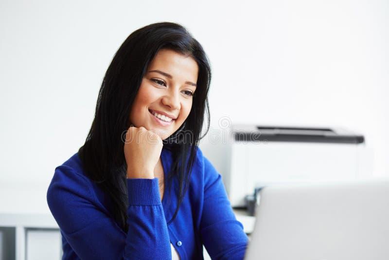 Kvinnasammanträde på skrivbordet som arbetar med bärbara datorn royaltyfri foto