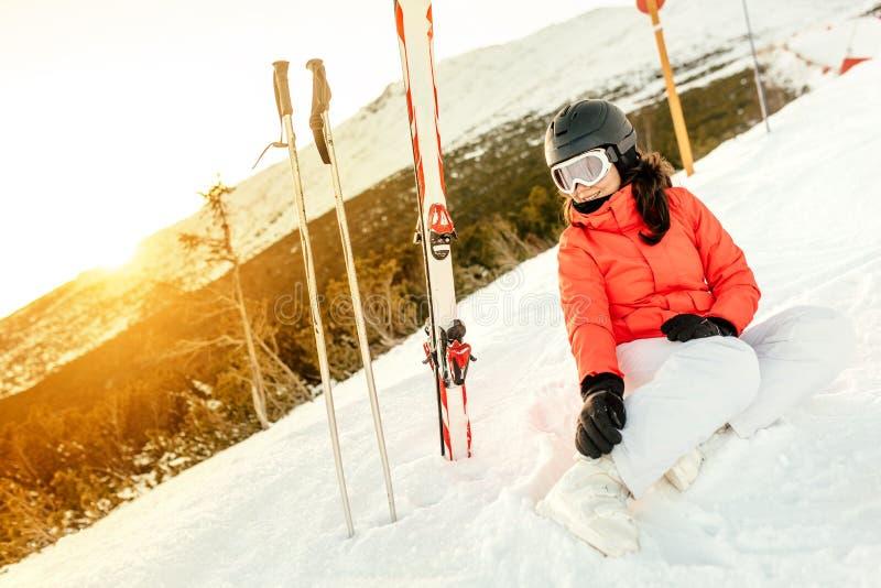 Kvinnasammanträde på snö som tycker om sikten från berg arkivfoto