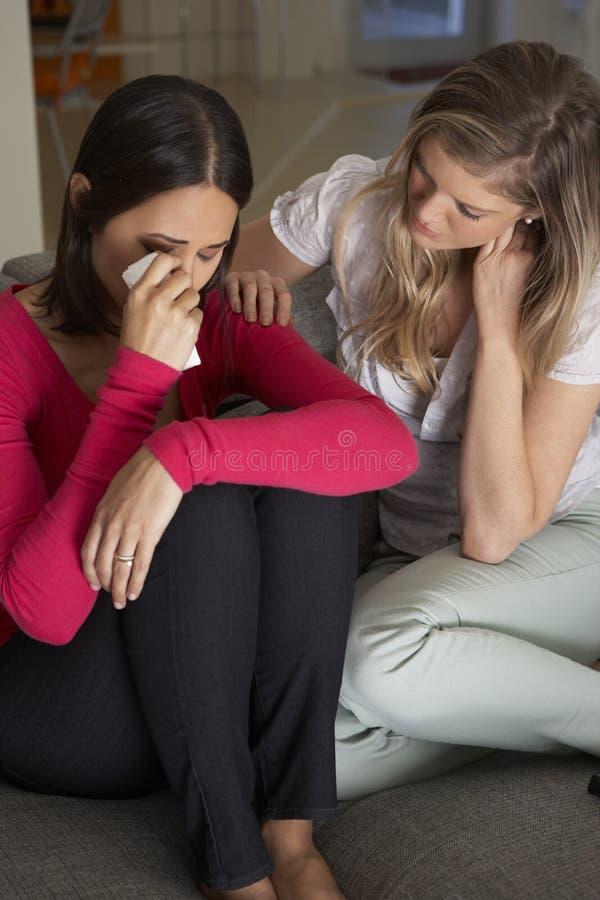 Kvinnasammanträde på Sofa Comforting Unhappy Friend royaltyfri foto