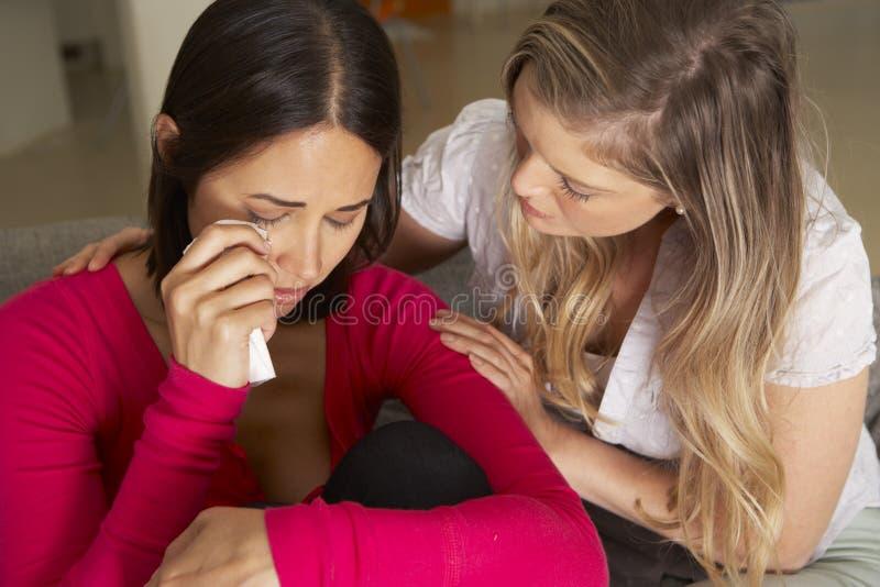 Kvinnasammanträde på Sofa Comforting Unhappy Friend fotografering för bildbyråer