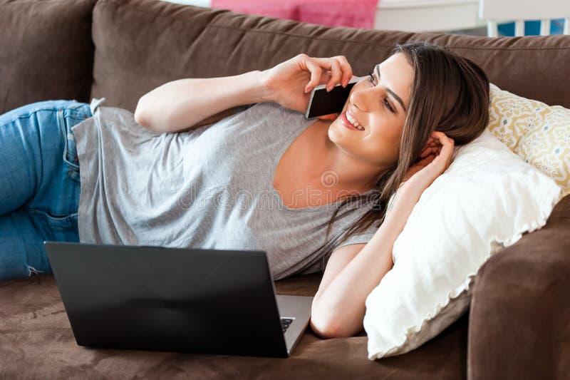 Kvinnasammanträde på soffan genom att använda modern teknologi arkivfoto