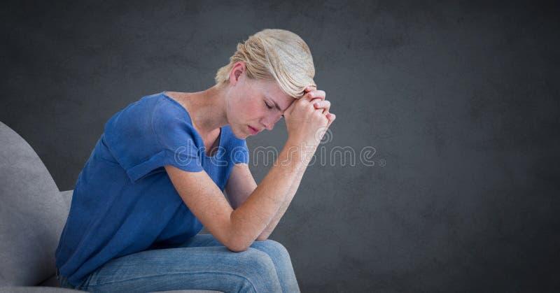 Kvinnasammanträde på soffan med huvudet på händer mot grå bakgrund med grungesamkopieringen fotografering för bildbyråer