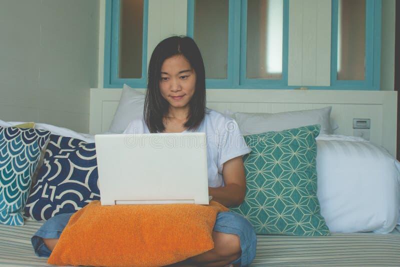 Kvinnasammanträde på soffan och spelabärbara datorn i sovrummet royaltyfri bild