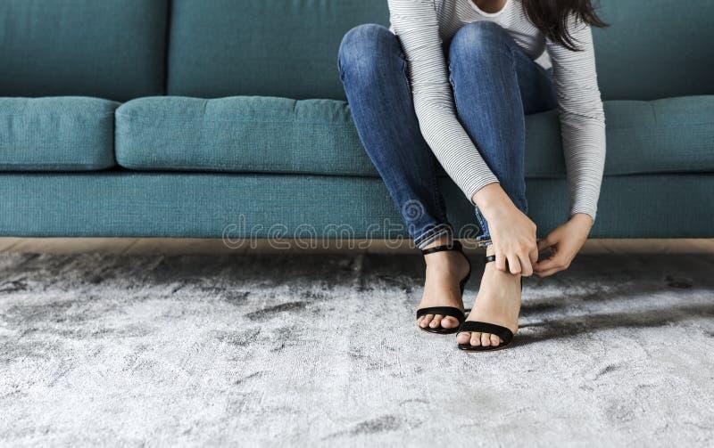 Kvinnasammanträde på soffan till att bära höga häl arkivbilder