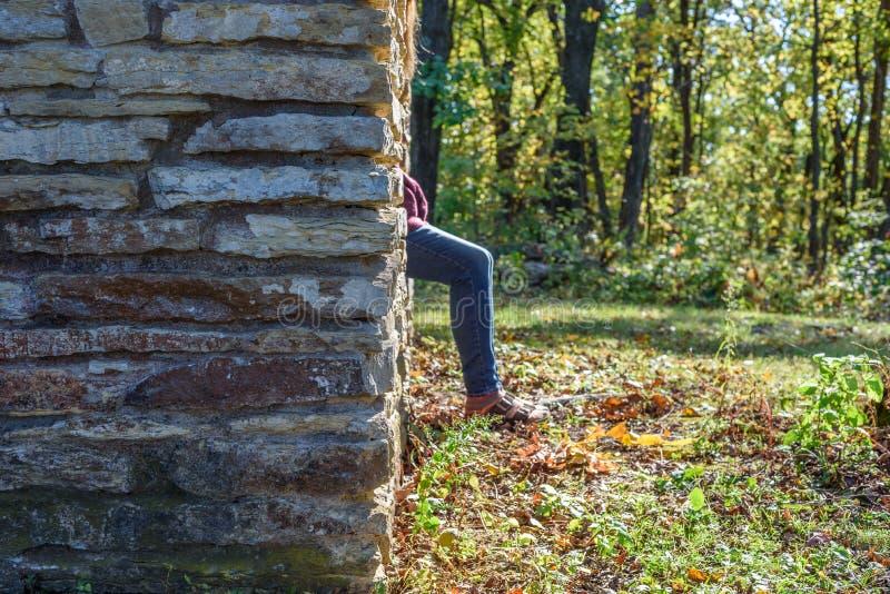 Kvinnasammanträde på stenavsatsen av skyddet i delstatspark i höst royaltyfri fotografi
