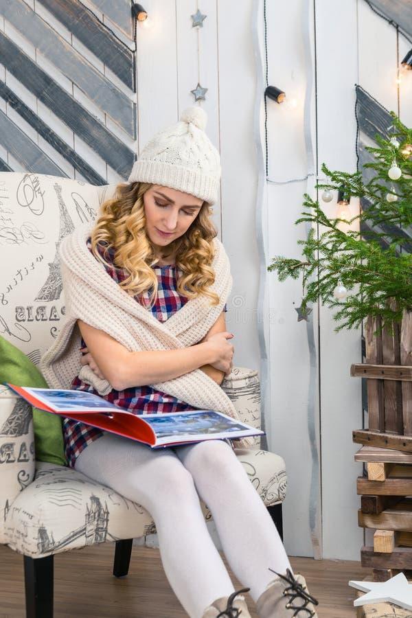 Kvinnasammanträde på stol och läsning en bok i det dekorerade rummet royaltyfri foto