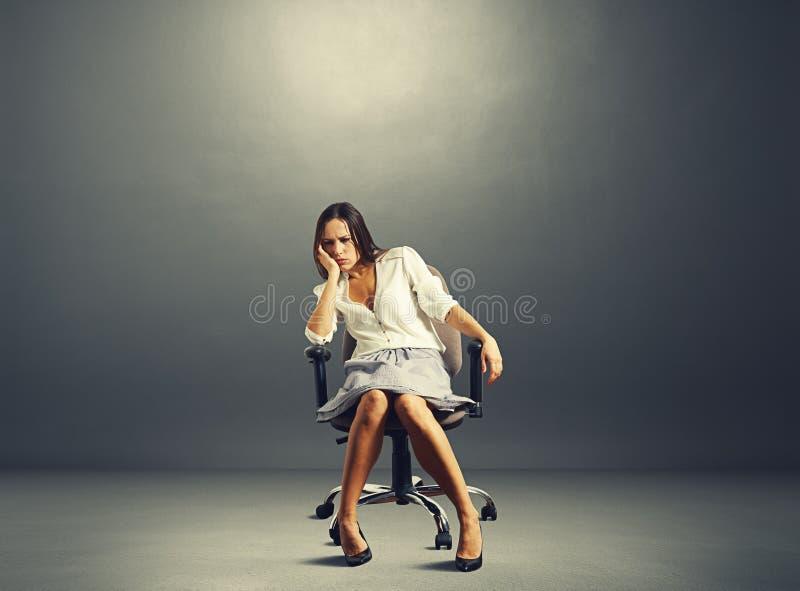 Kvinnasammanträde på stolen i tomt mörkt rum arkivfoton
